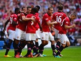 Manchester United's Robin Van Persie is congratulated by team mates after scoring the opening goal against Wigan during the Community Shield on August 11, 2013