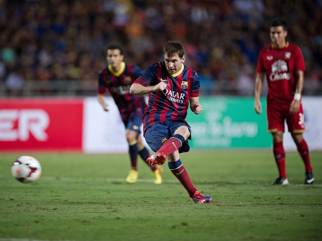 FC Barcelona's Lionel Messi takes a penalty shot against Thailand during their exhibition match with Thailand's national football team on August 6, 2013