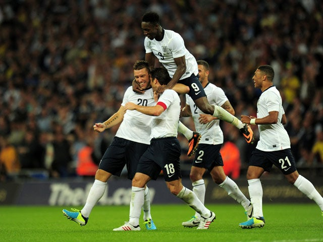 England's Rickie Lambert celebrates scoring the third goal against Scotland on August 14, 2013