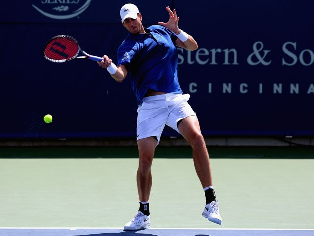 John Isner returns a shot to Milos Raonic of Canada during the Western & Southern Open on August 15, 2013
