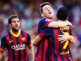 Barcelona's Lionel Messi is congratulated by team mate Pedro after scoring his team's second goal against Levante on August 18, 2013