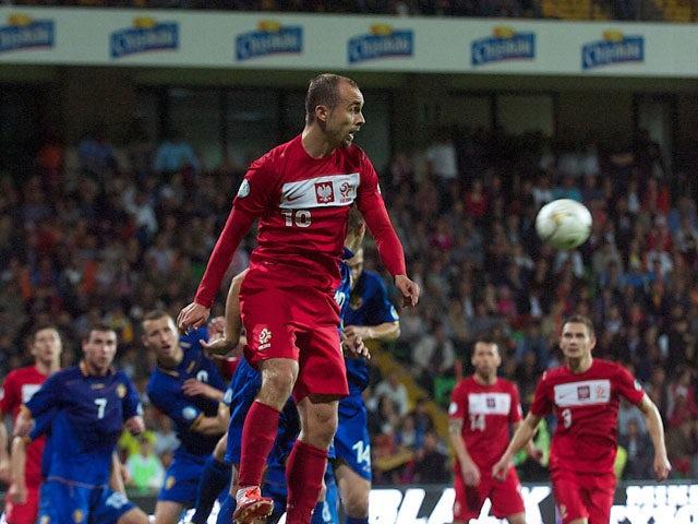 Poland's Piotr Zielinski jumps for the ball on June 7, 2013