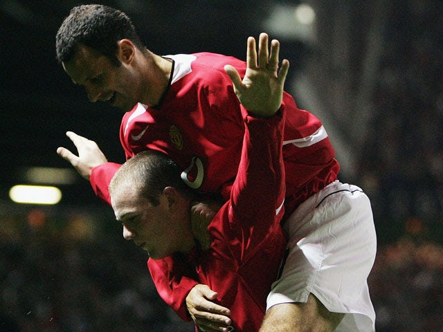Wayne Rooney of Manchester United celebrates his second goal with Ryan Giggs during the UEFA Champions League Group D match between Manchester United and Fenerbahce SK at Old Trafford on September 28, 2004