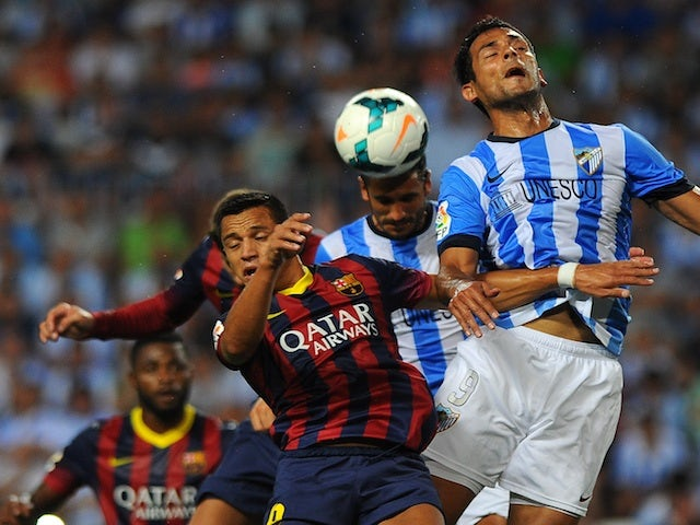 Players from Barcelona and Malaga battle for the ball during a game on August 25, 2013