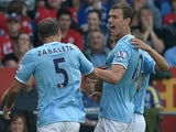 Manchester City's Edin Dzeko is congratulated by team mates after scoring the opening goal against Cardiff on August 25, 2013
