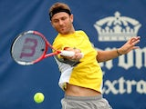 Mardy Fish returns a shot to Julien Benneteau of France during the Citi Open at the William H.G. FitzGerald Tennis Center on July 31, 2013