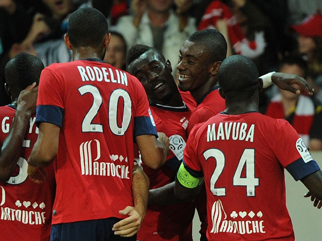 Lille's Salomon Kalou is congratulated by team mates after scoring the opening goal against Saint-Etienne on August 25, 2013