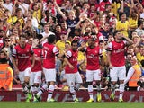 Arsenal's French striker Olivier Giroud celebrates with teammates after scoring the opening goal of the English Premier League football match between Arsenal and Tottenham Hotspur at the Emirates Stadium in London on September 1, 2013