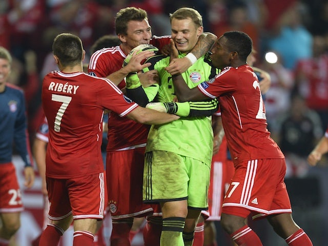 Bayern players congratulate Manuel Neuer after he saves Romelu Lukaku's penalty in the UEFA Super Cup final on August 30, 2013