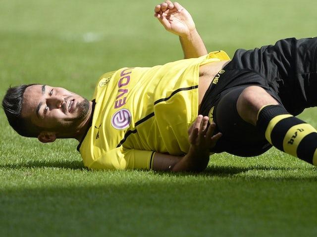 Dortmund's Ilkay Gundogan lies on the ground during a game with Augsburg on August 10, 2013