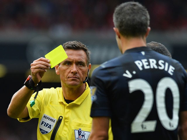 Referee Andre Marriner shows a Yellow card to Manchester United's Dutch striker Robin van Persie during the English Premier League football match between Liverpool and Manchester United at the Anfield stadium in Liverpool on September 1, 2013