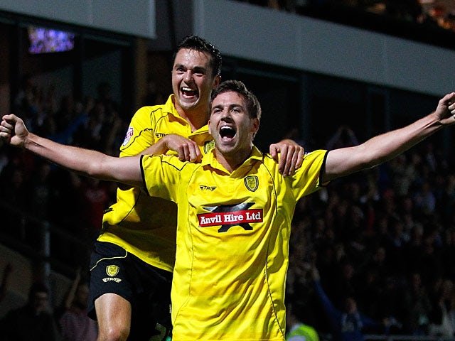 Burton's Michael Symes celebrates with team mate Jack Dyer after scoring his team's second goal against Fulham during their League Cup match on August 27, 2013