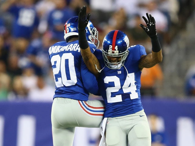 Prince Amukamara #20 of the New York Giants and Terrell Thomas #24 of the New York Giants celebrate a fumble recovery against the New York Jets during their pre season game at MetLife Stadium on August 24, 2013
