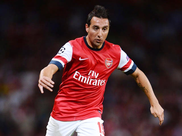 Santi Cazorla of Arsenal runs with the ball during the UEFA Champions League Play Off Second leg match between Arsenal FC and Fenerbahce SK at Emirates Stadium on August 27, 2013