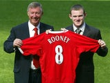 Sir Alex Ferguson and Wayne Rooney pose with the latter's shirt at his Manchester United unveiling.