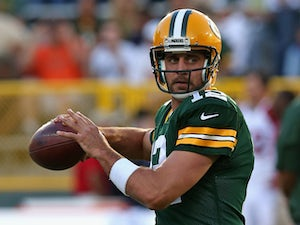 Aaron Rodgers #12 of the Green Bay Packers participates in warm-ups before a game against the Arizona Cardinals at Lambeau Field on August 9, 2013