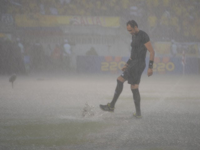 One of the referees inspects the field during a heavy downpour before the start of the Brazil 2014 FIFA World Cup South American qualifier match between Colombia and Ecuador, in Barranquilla, Colombia, on September 6, 2013