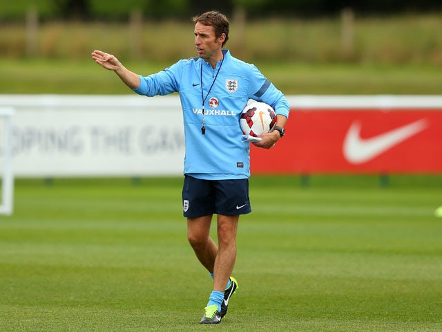 England Under-21 manager Gareth Southgate gives instructions to his players during a training session at St Georges Park on September 3, 2013