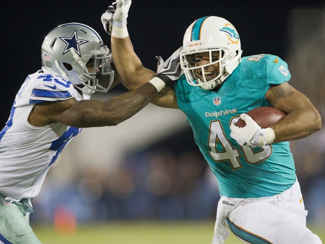 Defensive back Jakar Hamilton #43 of the Dallas Cowboys tries to tackle fullback Evan Rodriguez #48 of the Miami Dolphins during the third quarter at Fawcett Stadium on August 4, 2013