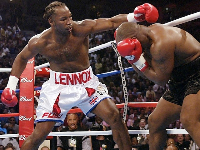 Lennox Lewis attempts to land a punch on Mike Tyson during their World Heavyweight Championship bout on June 8, 2002