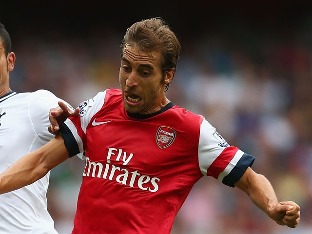 Nacer Chadli of Spurs and Mathieu Flamini of Arsenal battle for the ball during the Barclays Premier League match between Arsenal and Tottenham Hotspur at Emirates Stadium on September 01, 2013