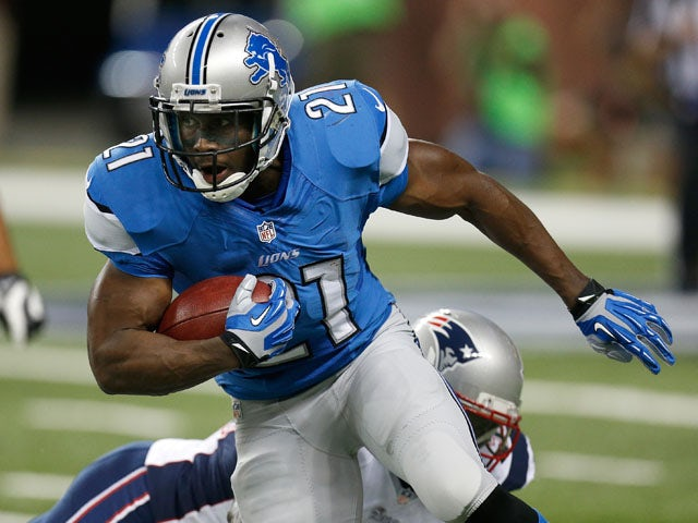 Reggie Bush #21 of the Detroit Lions looks to get around the tackle of Stevan Ridley #22 of the New England Patriots during a first quarter run during a pre season game at Ford Field on August 22, 2013