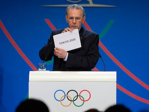 International Olympic Committee (IOC) President Jacques Rogge shows the name of the city of Tokyo elected to host the 2020 Summer Olympics during a session of the IOC in Buenos Aires, on September 7, 2013