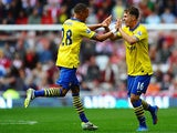Arsenal's Aaron Ramsey celebrates with team mate Kieran Gibbs after scoring his team's second goal against Sunderland on September 14, 2013