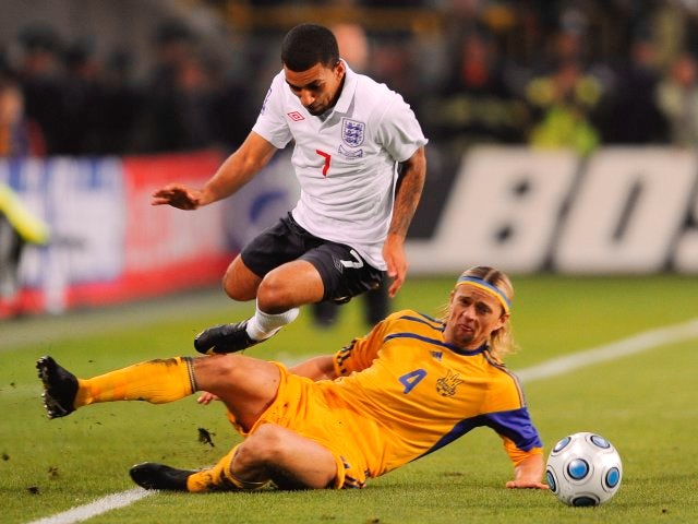Anatoliy Tymoshchuk performs a slide tackle on England winger Aaron Lennon.