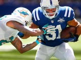 Donald Brown of the Indianapolis Colts runs the ball as Nolan Carroll of the Miami Dolphins reaches for the tackle at Lucas Oil Stadium on September 15, 2013