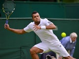 France's Jo-Wilfried Tsonga returns against Latvia's Ernests Gulbis in their second round men's singles match on day three of the 2013 Wimbledon Championships tennis tournament at the All England Club in Wimbledon, southwest London, on June 26, 2013