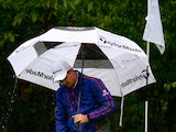 Justin Rose shelters himself from the rain at the BMW Championship on September 15, 2013