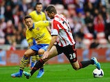 Arsenal's Mesut Ozil and Sunderland's Valentin Roberge battle for the ball on September 14, 2013