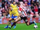 Arsenal's Mesut Ozil and Sunderland's Valentin Roberge battle for the ball on September 14, 2013