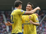 Arsenal's Olivier Giroud celebrates with team mate Mesut Ozil after scoring the opening goal against Sunderland on September 14, 2013