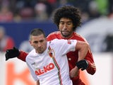 Augsburg striker Sascha Molders holds off a challenge from Bayern Munich defender Dante.
