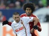 Augsburg striker Sascha Molders holds off a challenge from Bayern Munich defender Dante.