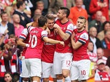 Arsenal's Aaron Ramsey is congratulated by teammates after scoring the opening goal against Stoke during their Premier League match on September 22, 2013