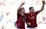 Roma's Adem Ljajic celebrates with teammate Marco Borriello after scoring his team's second goal against Lazio during their Serie A match on September 22, 2013