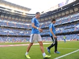 Real Madrid's Gareth Bale leaves the Bernabeu pitch during the warm-up after injuring himself prior to the game with Getafe on September 22, 2013