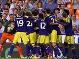 Swansea's Jonathan de Guzman is mobbed by team mates after scoring his team's third goal against Valencia during their Europa League group match on September 19, 2013