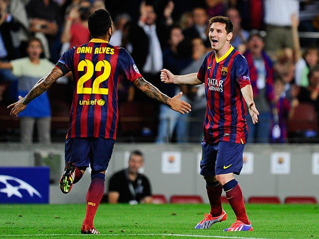 6ff9fef5928 Barcelona's Lionel Messi is congratulated by team mate Dani Alves after  scoring the opening goal against Ajax during their Champions League group  match on ...