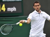 Marin Cilic returns against Marcos Baghdatis on his way to victory in their men's first round match at Wimbledon on June 24, 2013
