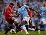 Manchester United's Wayne Rooney and Manchester City's Yaya Toure battle for the ball during their Premier League match on September 22, 2013