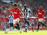 Shinji Kagawa of Manchester United breaks free from Youssuf Mulumbu of West Bromwich Albion during the Barclays Premier League match between Manchester United and West Bromwich Albion at Old Trafford on September 28, 2013