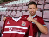 New Northampton Town signing Paul Reid poses with a shirt during a photo call at Sixfields Stadium on September 27, 2013