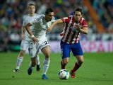 Angel Di Maria of Real Madrid CF competes for the ball with Koke of Atletico de Madrid during the La Liga match between Real Madrid CF and Club Atletico de Madrid at Estadio Santiago Bernabeu on September 28, 2013