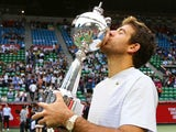 Winner Juan Martin Del Potro of Argentina kisses his trophy at trophy ceremony after winning his men's singles final match against Milos Raonic of Canada on day seven of the Rakuten Open at Ariake Colosseum on October 6, 2013