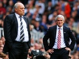 Fulham manager Mark Hughes looks on as Stoke boss Martin Jol watches the Barclays Premier League game between their sides on October 5, 2013