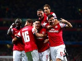 Arsenal's Mesut Ozil is congratulated by teammates after scoring the opening goal against Napoli during their Champions League group match on October 1, 2013